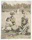 A well-dressed Japanese-American couple sits on the grass with their two young children